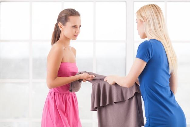 Questo vestito è mio! due giovani donne arrabbiate che tengono insieme un vestito e si guardano