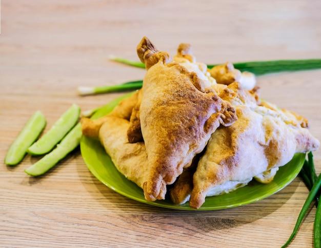 Questo è un vero samsa uzbeko su un piatto con verdure e cipolle verdi. cucina nazionale