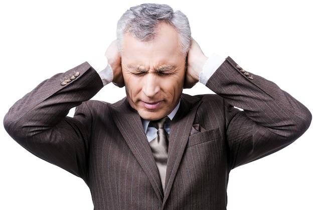 Questo è troppo rumoroso! uomo maturo frustrato in abiti da cerimonia che tiene la testa tra le mani e tiene gli occhi chiusi mentre sta in piedi su sfondo bianco