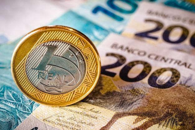 In questa illustrazione fotografica vengono visualizzate centoduecento banconote reais e una moneta da un reais evidenziata. il real è il denaro corrente in brasile.