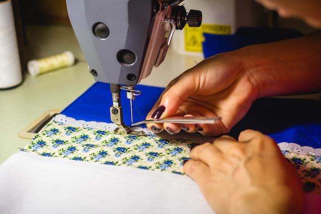 In questa illustrazione fotografica una sarta che infila una macchina da cucire per lavorare nel laboratorio di moda.