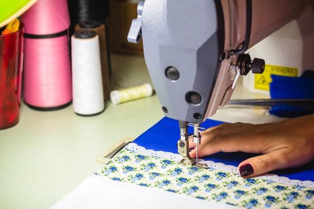 In questa illustrazione fotografica una sarta che lavora alla macchina da cucire nel laboratorio di moda.