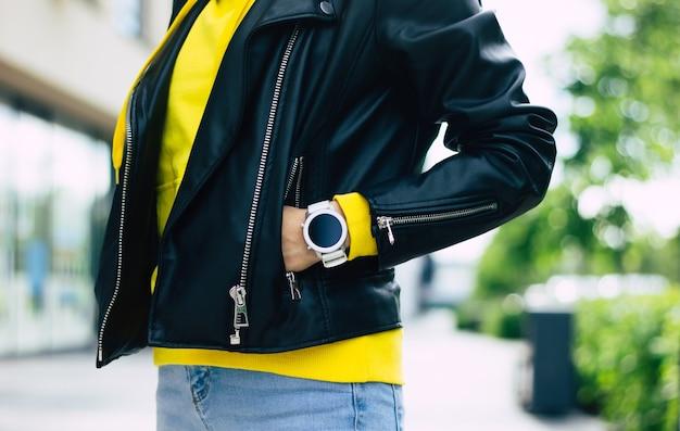 Questo smartwatch è adatto a me! aspetto di una giovane donna, che consiste nel suo nuovo smartwatch moderno, giacca di pelle e felpa con cappuccio gialla.