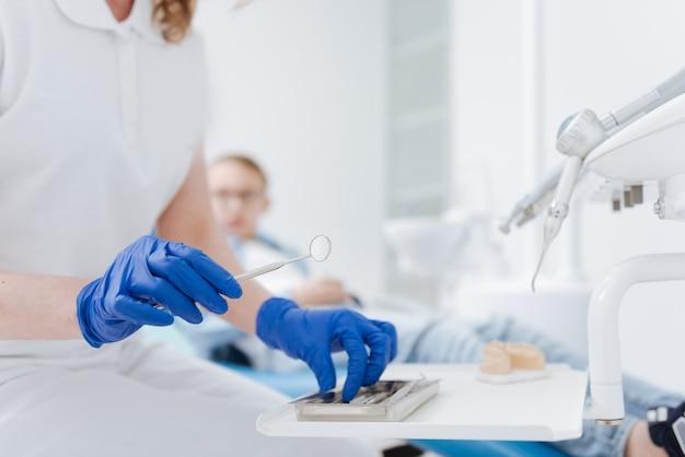 Medico di successo determinato a fondo che avvia una procedura di controllo dei denti dei suoi pazienti prima di prescrivere qualsiasi trattamento