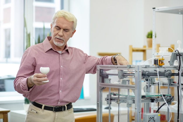 Esame approfondito. affascinante uomo anziano che scruta un modello realizzato con una stampante 3d appoggiandosi leggermente su di esso