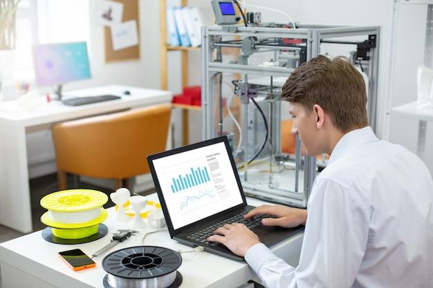 Preparazione accurata. affascinante giovane uomo seduto al suo posto di lavoro in ufficio e creando una presentazione sul computer portatile, preparandosi a tenere un discorso