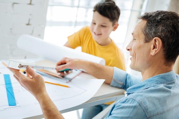 Operaio accurato. bel giovane uomo seduto al tavolo con suo figlio, lavorando sul progetto e controllando le misure su nastro