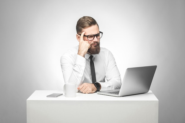 Il giovane capo barbuto premuroso in camicia bianca e cravatta nera è seduto in ufficio sulla scrivania e guarda il rapporto quotidiano sul laptop, ha una nuova idea e pianifica la propria strategia, tenendo una mano sulla testa.