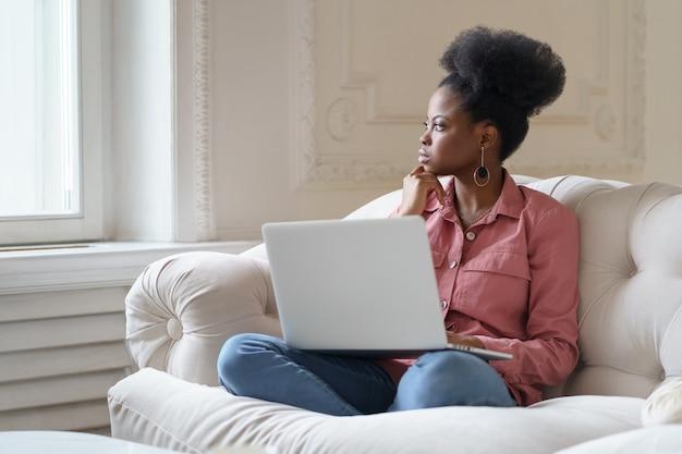 Premurosa donna africana seduta sul divano a casa, distratta dal lavoro del laptop guardando fuori dalla finestra