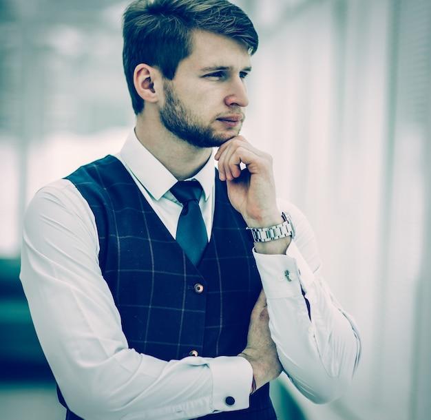 Imprenditore principiante premuroso in piedi vicino alla finestra