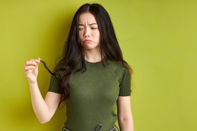 Premurosa donna bruna sta guardando le doppie punte dei capelli, esaminarlo, vuole tagliare, provare emozioni tristi, sfondo verde isolato