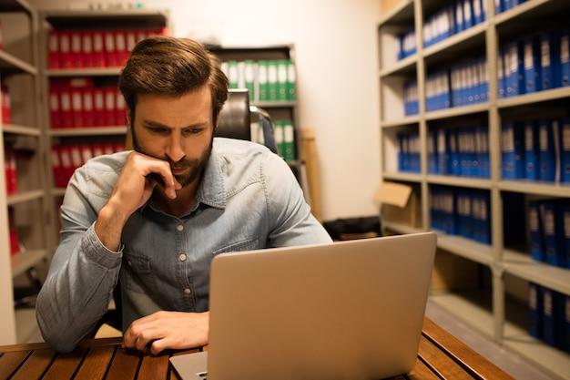 Uomo d'affari premuroso utilizzando laptop nella stanza di archiviazione di file