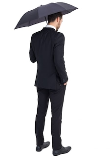 Uomo d'affari premuroso sotto l'ombrello con la mano in tasca