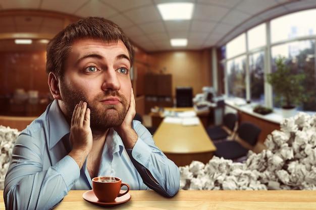 Uomo d'affari premuroso con una grande testa che beve caffè in ufficio