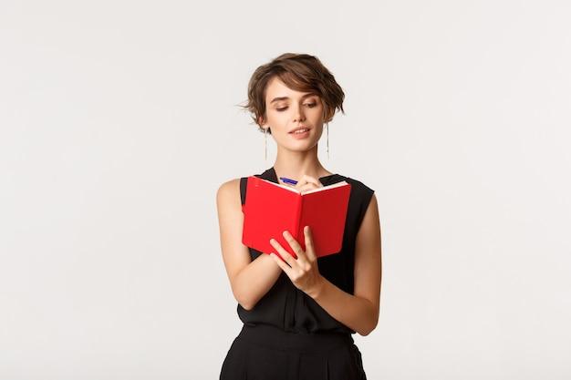 Programma di pianificazione della donna di affari premurosa nel taccuino, scrivendo qualcosa nel pianificatore, levantesi in piedi sopra bianco.