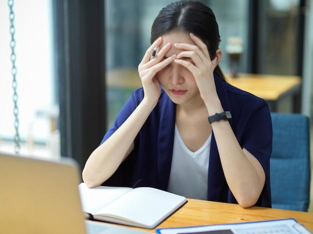 Donne d'affari premurose che lavorano alla sua scrivania in ufficio e si sentono stanche del lavoro, mal di testa, depressione, stanche di trovare soluzioni per risolvere i problemi aziendali, stressate