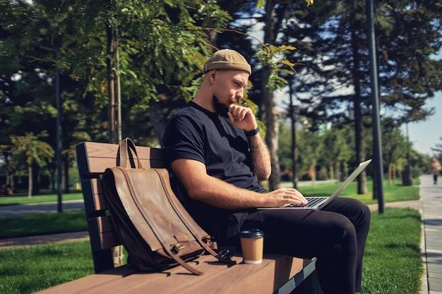 L'uomo d'affari libero professionista caucasico premuroso si siede sulla panchina con il computer portatile mentre lavora da remoto