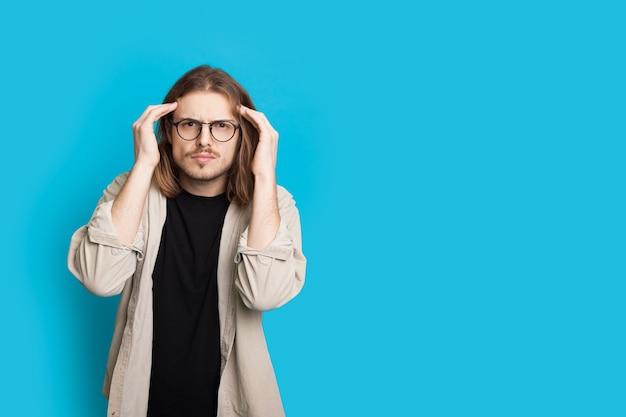 Uomo caucasico premuroso con capelli lunghi e occhiali da vista sta toccando la sua testa e guardando la telecamera su una parete blu dello studio con spazio libero