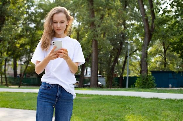 Premurosa donna caucasica freelance in abiti casual che naviga nel telefono cellulare mentre si cammina nel parco