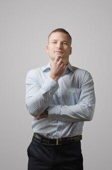 Giovane uomo d'affari premuroso e allegro sulla superficie bianca.