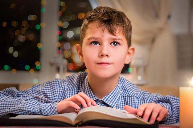 Bambino premuroso con un libro. bambino con libro vicino alla finestra. in attesa di una nuova idea. la vacanza porterà buoni pensieri.