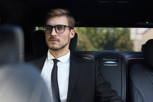Uomo d'affari premuroso fiducioso in abito completo con occhiali che guarda lontano mentre è seduto in macchina.
