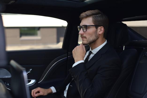 Uomo d'affari premuroso fiducioso che tiene la mano sugli occhiali mentre è seduto nell'auto di lusso.