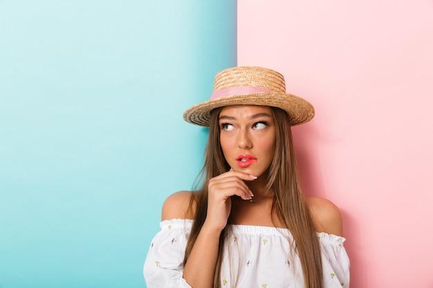 Giovane bella donna confusa premurosa che posa cappello d'uso isolato.