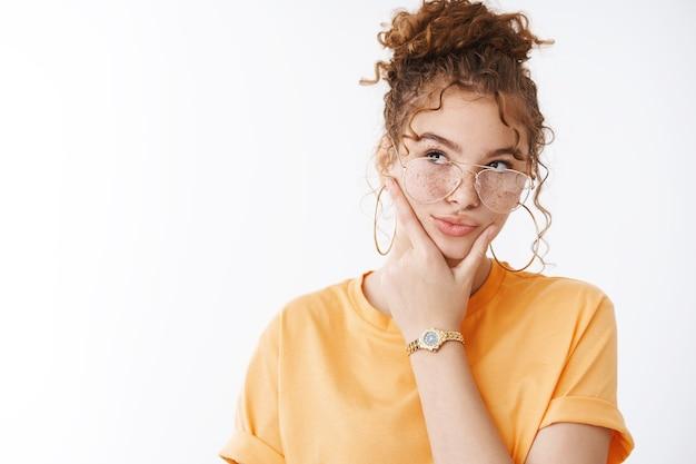 Premurosa creativa attraente rossa dai capelli ricci blogger femminile che pensa al trucco nuove idee di contenuto sembra focalizzata prendere decisione scelta sfregamento mento aspetto esitante in alto a sinistra, sfondo bianco