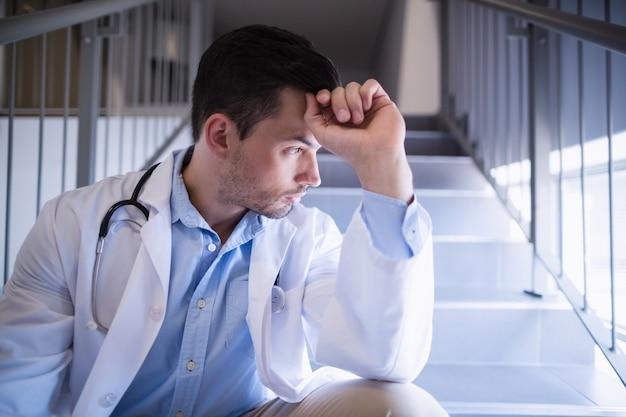 Medico premuroso che si siede sulla scala