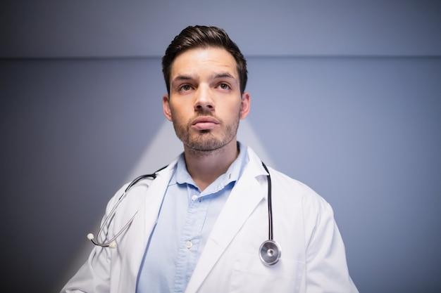 Medico premuroso che sta in corridoio