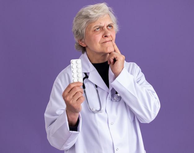 Premurosa donna anziana in uniforme da medico con stetoscopio tenendo la confezione della pillola e guardando in alto isolato su parete viola