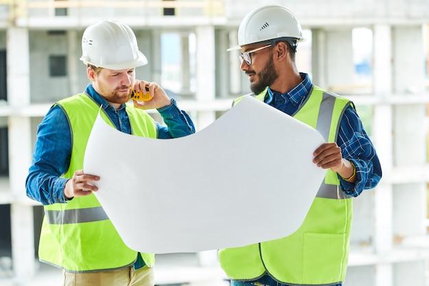 Ingegneri premurosi che analizzano il piano di costruzione