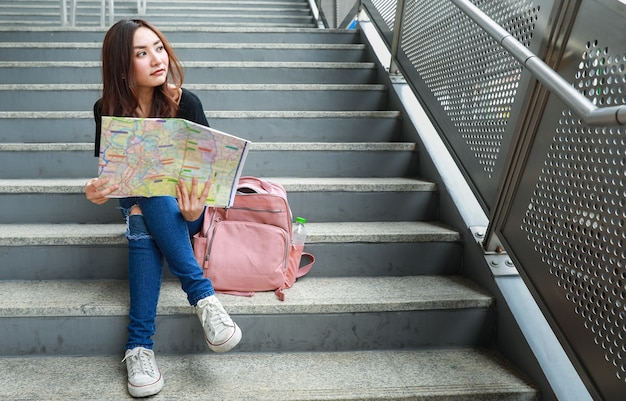 Viaggiatore femminile etnico premuroso che si siede sulle scale con la mappa di carta e distogliere lo sguardo. concetto di viaggio e comunicazione nella vita di città