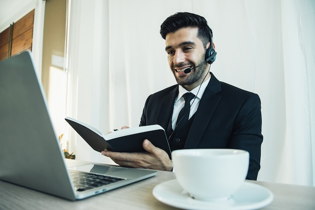 L'uomo d'affari premuroso e bello del call center pensa al progetto online guardando il laptop sul posto di lavoro