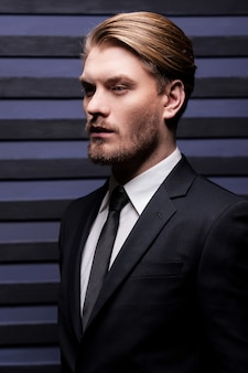 Bello premuroso. vista laterale di un bel giovane in abiti da cerimonia che guarda lontano mentre si trova su uno sfondo a strisce