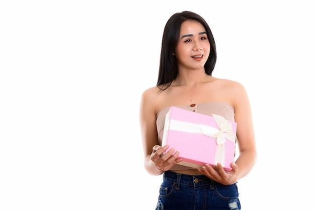 Donna asiatica felice premurosa del transgender che sorride mentre tiene il contenitore di regalo