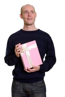 Uomo caucasico calvo felice premuroso che sorride e che tiene il contenitore di regalo