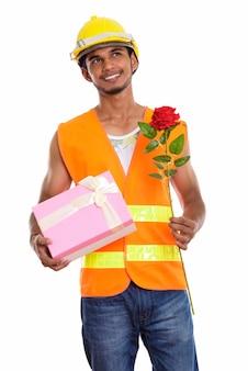 Operaio edile indiano felice premuroso dell'uomo che sorride mentre tiene la rosa rossa e il contenitore di regalo. concetto di san valentino