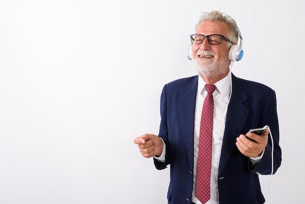 Premuroso felice senior barbuto imprenditore sorridente mentre si tiene il telefono cellulare e l'ascolto di musica su bianco