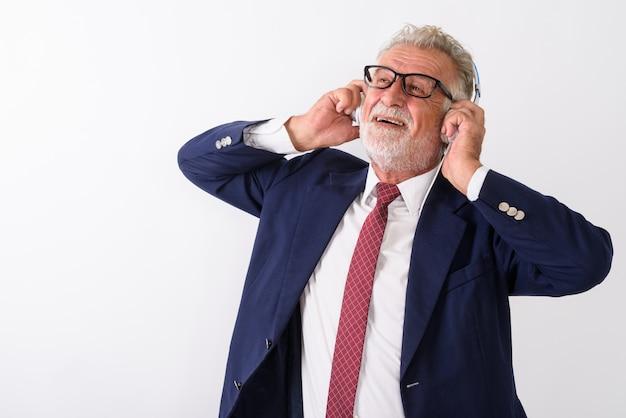 Premuroso felice senior barbuto imprenditore sorridente durante l'ascolto di musica e tenendo le cuffie su bianco