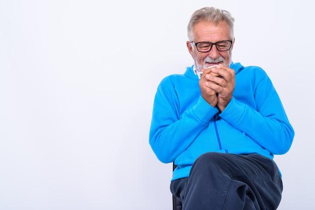 Premuroso felice senior barbuto uomo sorridente mentre si tiene la tazza di caffè vicino al viso e seduto su una sedia pronto per la palestra su bianco