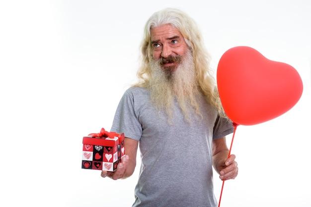 Uomo barbuto senior felice premuroso che sorride mentre tiene heeart rosso