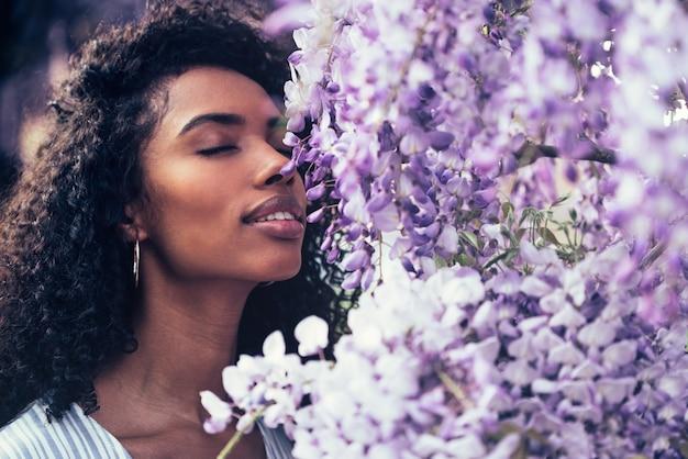 Giovane donna di colore felice premurosa circondata dai fiori