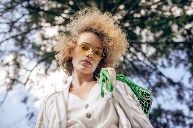 Sguardo premuroso. giovane donna dai capelli riccia in un parco che sembra pensierosa