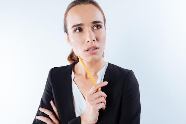 Sguardo premuroso. bella bella donna premurosa che tiene una matita e pensa al suo problema mentre osserva da parte