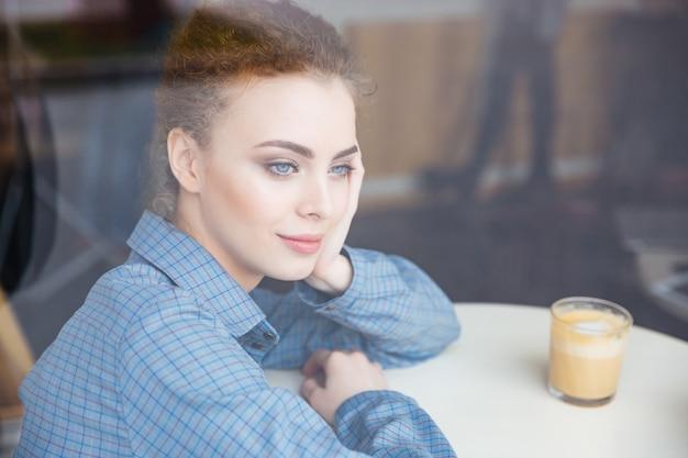 Giovane donna adorabile premurosa sulla camicia blu che beve caffè e che pensa in caffè