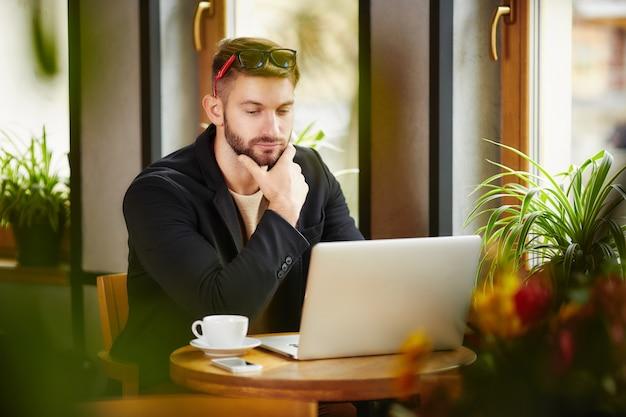 Uomo premuroso al computer portatile nella caffetteria