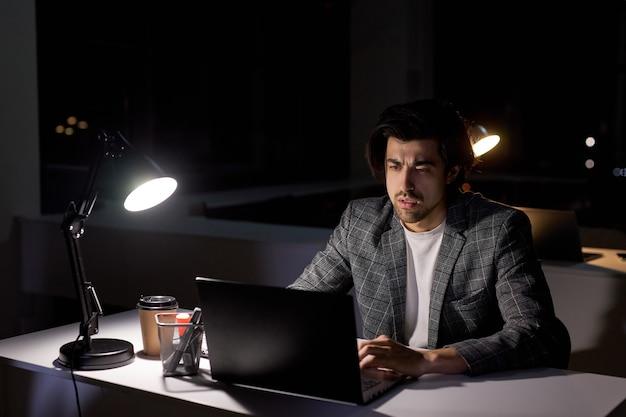 Uomo premuroso leggere il piano aziendale sul computer, pensando a domanda o attività da capo, uomo che realizza la quantità di lavoro in ufficio a tarda notte, vista laterale. nella stanza buia dell'ufficio
