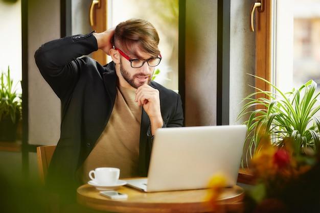 Uomo premuroso che graffia testa al computer portatile